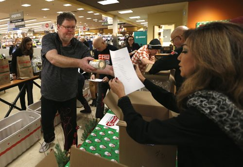 At left, Free Press columnist Doug Speirs and Tracy Koga with Shaw TV compete in the media challenge to fill the list for a 3 person hamper as quickly as possible.  This event was to highlight the Christmas Cheer Board  grocery donation Safeway paper bag delivered in the Winnipeg Free Press to homes in Winnipeg Tuesday. People can fill up the paper bags with non-perishables or purchase $5 and $10 care packages and the Safeway store will take them to the Cheer Board. Doug Speirs  story Wayne Glowacki / Winnipeg Free Press Dec.1 2015