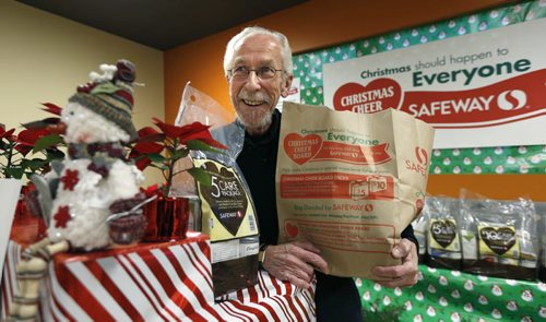 Kai Madsen with the Christmas Cheer Board holds a Christmas Cheer grocery donation Safeway paper bag like one of the 53,600 bags delivered in the Winnipeg Free Press to homes in Winnipeg Tuesday. People can fill up the paper bags with non-perishables or purchase $5 and $10 care packages and the Safeway store will take them to the Cheer Board. Doug Speirs  story Wayne Glowacki / Winnipeg Free Press Dec.1 2015