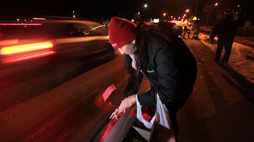 """Althea Guiboche places ribbons along the guard rails of the Slaw Rebchuk bridge Monday evening. The Red RIbbon Project she's spearheading is to honor of all of the Missing and Murdered of Canada, Althea Guiboche """"The Bannock Lady"""" will be leading a red cloth memorial project for the bridges around Winnipeg. See Ashley Prest story. December 14, 2015 - (Phil Hossack / Winnipeg Free Press)"""