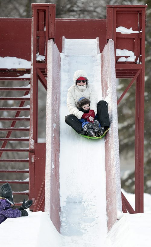 Laurie Boutin and her son Olivier (2) zoom down the toboggan slide enjoying a frosty Christmas morning in Kildonan Park.Sister Juliette (7) cheers from the sidelines at the bottom of the slide.  Laurie and her family are visiting her parents in the city while back at their Toronto home golfers are enjoying +15C WEATHER. December 25, 2015 - (Phil Hossack / Winnipeg Free Press)
