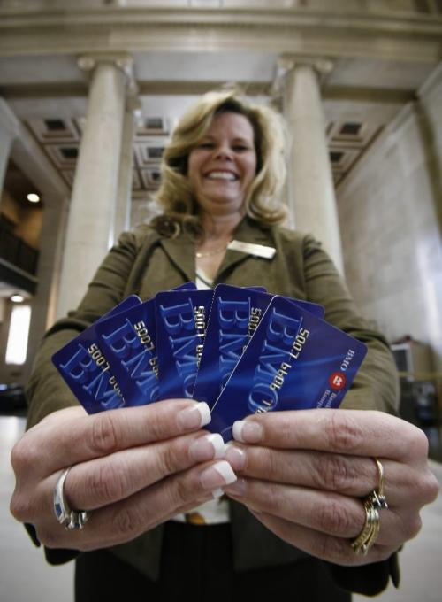 John Woods / Winnipeg Free Press / February 8, 2008- 080208  - Yvonne Couvier, Bank of Montreal Main/Portage branch manager , poses for a photograph with some bank cards Friday, February 8, 2008.  The cards will be phased out in the near future.