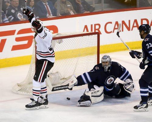TREVOR HAGAN / WINNIPEG FREE PRESS Chicago Blackhawks' Andrew Ladd (16) scores on Winnipeg Jets' goaltender Ondrej Pavelec (31) with Dustin Byfuglien (33) in front of the net during third period NHL hockey action, Friday, March 18, 2016.