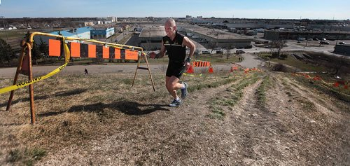 """PHIL HOSSACK / WINNIPEG FREE PRESS Grimacing all the way, Vic Keller trains running up the steep part of Westview Park's """"Garbage Hill""""  Tuesday evening. The city is going to repair erosion from cyclists and runners sprinting up the grassy slope. Geoff Kirbyson's story April 26, 2016"""