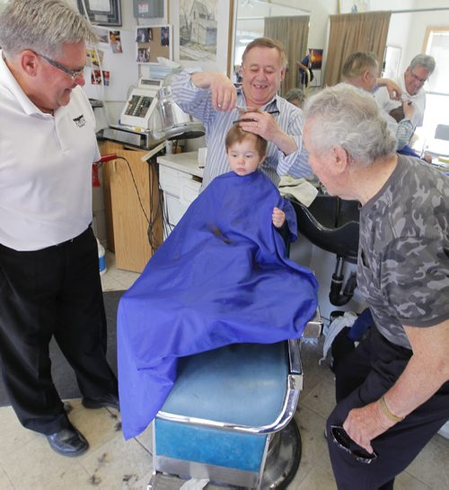BORIS MINKEVICH / WINNIPEG FREE PRESS (centre) Barber Rocky Curatola of Rocky's Men's Hair Styling cuts a fifth generation customer Lincoln Alto, just shy of 2 years old, while grandpa (left) Dr. Lauri Alto, 61, and great grandpa (right) Olie Alto, 87, watch on. This is the boys 3rd haircut. The boys dad couldn't make it down for the photo because of work, but grandpa and great gramps were happy to help pass down the family tradition. Great Great Grandfather Lauri Alto passed away. Photo taken at the barber shop's current location at 290 Pembina Highway. May 19, 2016.