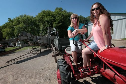 PHIL HOSSACK / WINNIPEG FREE PRESS - Barry Klym's daughters Angioe (left) and Erin pose on a McCormick Farmall tractor Tuesday afternoon.  Barry's taking the machines and his daughters to the Austin Thresherman's Reunion where the family passion for antique farm equipment will be on display. - See Bill Redekop story. June 28, 2016