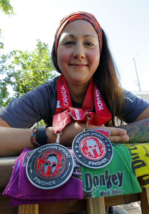 BORIS MINKEVICH / WINNIPEG FREE PRESS Ashleigh Sanduliak poses with some medals and swag from some events she participated in lately. She's run the Dirty Donkey Mud Run for the last four years and has recently started doing the Spartan mud runs as well.  July 22, 2016