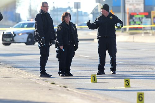 RUTH BONNEVILLE / WINNIPEG FREE PRESS  Police Identification officers investigate shooting scene on  Stradbrook Ave where 6 shot were fired at a vehicle around 3am Saturday morning sending two people to the hospital. Donald street north bound has markers on it identifying ammunition shells from shooting.    Nov 26, 2016