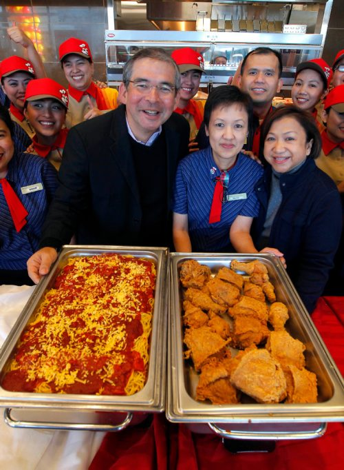 BORIS MINKEVICH / WINNIPEG FREE PRESS Jollibee Foods Corporation (JFC), the world's 9th largest restaurant company, brings an early Christmas gift to Canadians as it opens its first-ever store in the country on Ellice Ave. in Winnipeg tomorrow. (front row) Jollibee Foods Corporation Group President Jose A. Miñana Jr., left, Ellice restaurant manager Belva Recio, middle, and Jollibee USA Vice President / General Manager Maribeth D. dela Cruz, right, poses with Jolly Spaghetti and Jolly Crispy Chicken while staff gather around in the background. REBECCA DAHL STORY  Dec. 14, 2016