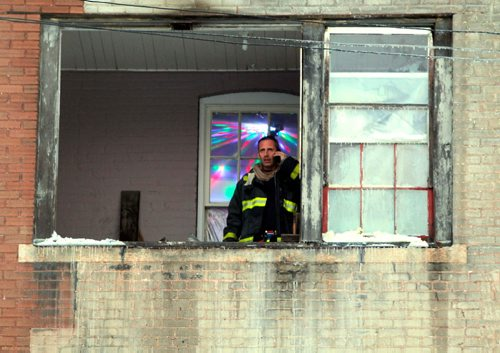 BORIS MINKEVICH / WINNIPEG FREE PRESS A firefighter looks out the window of a third floor apartment in the rear of 181 Balmoral Street. A fire broke out in the apartment this afternoon. Photo taken after fire was out and the last crew was packing up.  JAN. 12, 2017