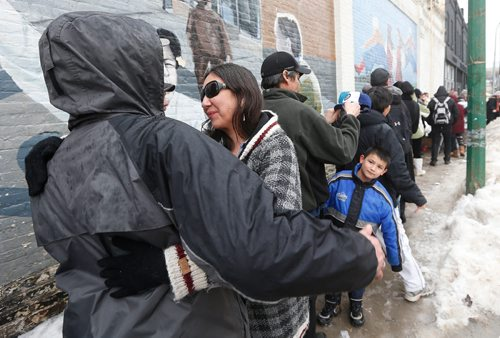 """JOHN WOODS / WINNIPEG FREE PRESS On Dufferin at Main, Althea Guiboche, AKA """"The Bannock Lady"""", hugs people who line up to receive food Sunday, January 22, 2017. Guiboche and her crew of dedicated supporters are marking four years of feeding local people."""