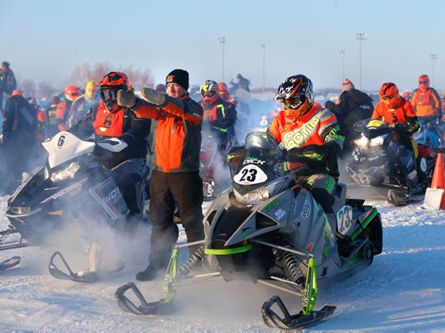 WAYNE GLOWACKI / WINNIPEG FREE PRESS   Eighty riders from Canada and the U.S. were warming up their engines at the start of the 2017 USXC I-500 cross country snowmobile race from Winnipeg to Bemidj, MN. in the -29C temperature Wednesday morning. Draper Lundquist directs the next 2 riders to the starting line at the Red River Co-op Speedway, this race has some of the world's best snowmobile racers competing for more than 500 miles over some of the toughest terrain Mother Nature can create. Feb. 8  2017