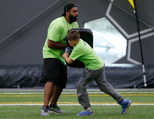 JOHN WOODS / WINNIPEG FREE PRESS Former Blue Bomber Obby Khan holds the bag during a drill for the young players at the Doug Brown KidSport Winnipeg Football Camp at the University of Winnipeg Sunday, May 28, 2017.