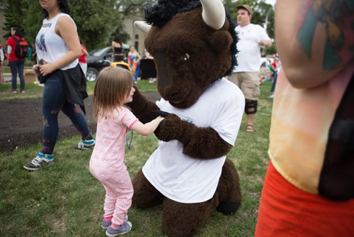 JEN DOERKSEN/WINNIPEG FREE PRESS A child plays with the bison mascot from the University of Manitoba float at the 30th annual Pride Parade. Sunday, June 4, 2017.