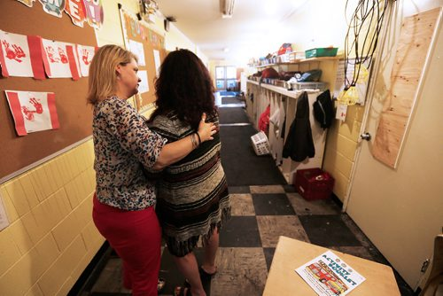 JOHN WOODS / WINNIPEG FREE PRESS Cathy Somerset (R), acting executive director, St Therese Child Care Facility is comforted by Shannon McNeill, Parent and treasurer in the smoke damaged hallway of the facility Monday, July 3, 2017. The child care facility was damaged by a fire.