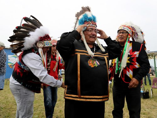 TREVOR HAGAN / WINNIPEG FREE PRESS Southern Grand Chief Jerry Daniels, AMC Grand Chief Arlen Dumas, and Brokenhead Chief Jim Bear help Peguis Chief Glenn Hudson put on a headdress presented to him from Lord Selkirk, Friday, July 21, 2017.