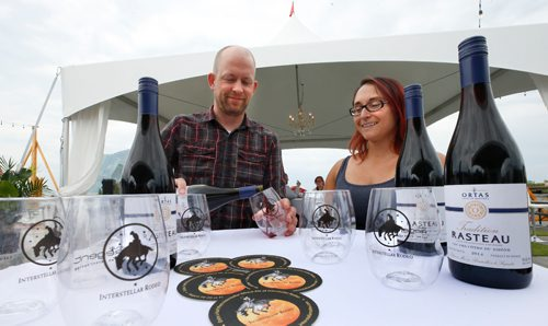 """WAYNE GLOWACKI / WINNIPEG FREE PRESS  Interstellar Rodeo Wine curator Ben MacPhee-Sigurdson pours a glass of French red wine beside Kim Bamburak with Kenaston Wine Market who supplies Ortas Tradition Rasteau that is paired with Father John Misty for this year's Interstellar Rodeo August 18-20 at The Forks. This wine choice is """"multi-layered, complex but very open and honest like performer Father John Mist."""" At this preview event held on the parkade at The Forks Tuesday provided details of this year's artist-and-wine pairings and food offerings, which include individual artist pairings, new house wines for 2017 and exclusive 'Interstellar Rodeo' food items offered by select vendors Ben, also the Wine columnist with the Winnipeg Free Press shared some notes at the event on his selection process this year. August 8 2017"""