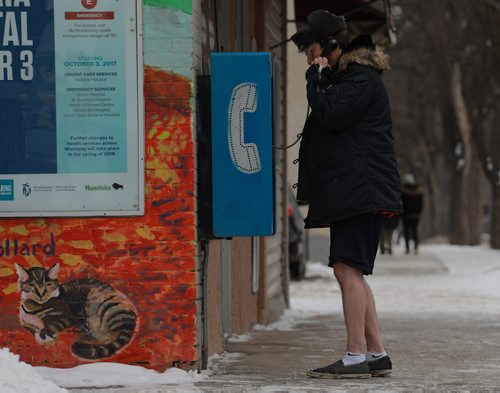 COLIN CORNEAU / WINNIPEG FREE PRESS Matthew Frost makes a call from a Wolseley Avenue payphone. Frost had inadvertently locked his way out of his nearby apartment and reached out to a friend before the cold got to him. November 12, 2017