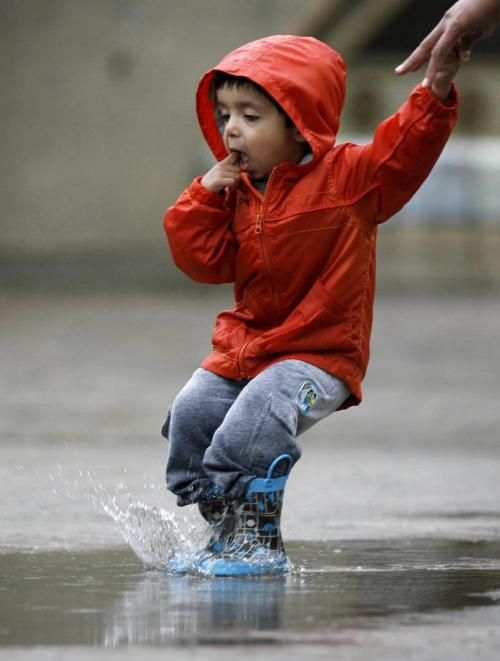 MIKE.DEAL@FREEPRESS.MB.CA 100528 - Friday, May 28th, 2010 Two-year-old Ajai Sandhu jumps in the puddles from this mornings thunder showers while on a visit to The Forks. MIKE DEAL / WINNIPEG FREE PRESS