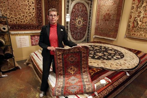BORIS.MINKEVICH@FREEPRESS.MB.CA  100825 BORIS MINKEVICH / WINNIPEG FREE PRESS Ten Thousand Villages manager Gwen Repeta poses for a photo with some rugs they sell that were made in Pakistan.