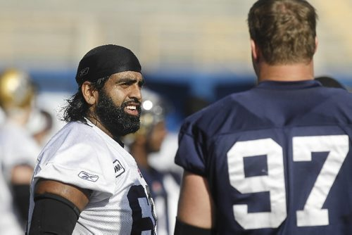 """TREVOR HAGAN / WINNIPEG FREE PRESS - Bomber Centre, Ibrahim """"Obby"""" Khan, chats with Doug Brown during practice today at CanadInns Stadium. 10-10-09"""