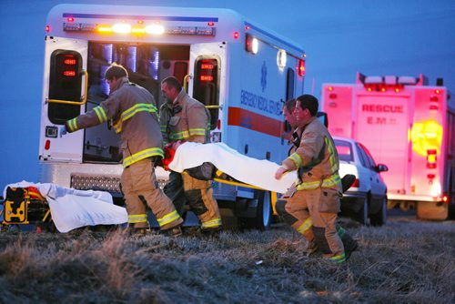 Brandon Sun 16112010 Brandon Fire and Emergency Services members carry the driver of a Jeep to a waiting ambulance after a single vehicle rollover on Veterans Way east of Brandon on Tuesday evening. The driver was taken to hospital with non-life-threatening injuries. (Tim Smith/Brandon Sun)