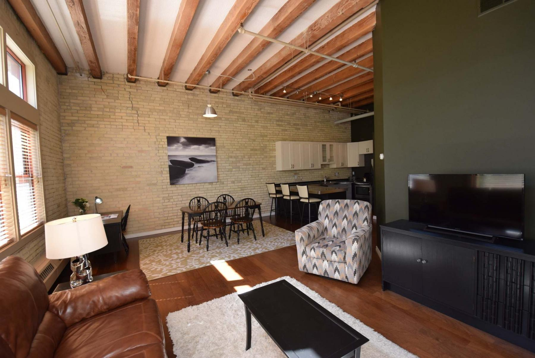 <p>PHOTOS BY TODD LEWYS / WINNIPEG FREE PRESS</p><p>The beams and exposed brick of the condo&rsquo;s great room recall the history of the Ashdown Warehouse.</p>