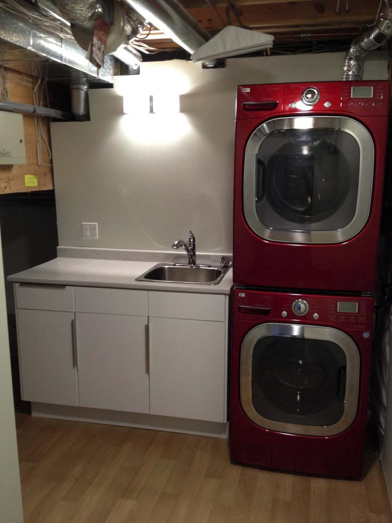 <p>The stackable washer and dryer are positioned near the exterior wall with the vanity and sink placed adjacent, providing countertop space.</p></p>