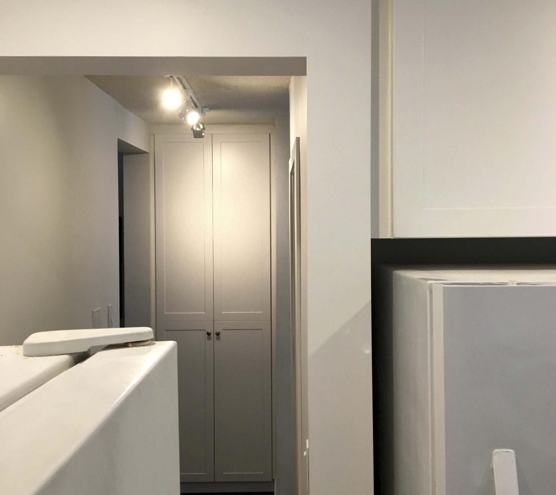 <p>Because the cupboard/pantry matches the new kitchen cupboards, it appears as a mere extension of the kitchen space even though it is located at the other end of the hall. </p>