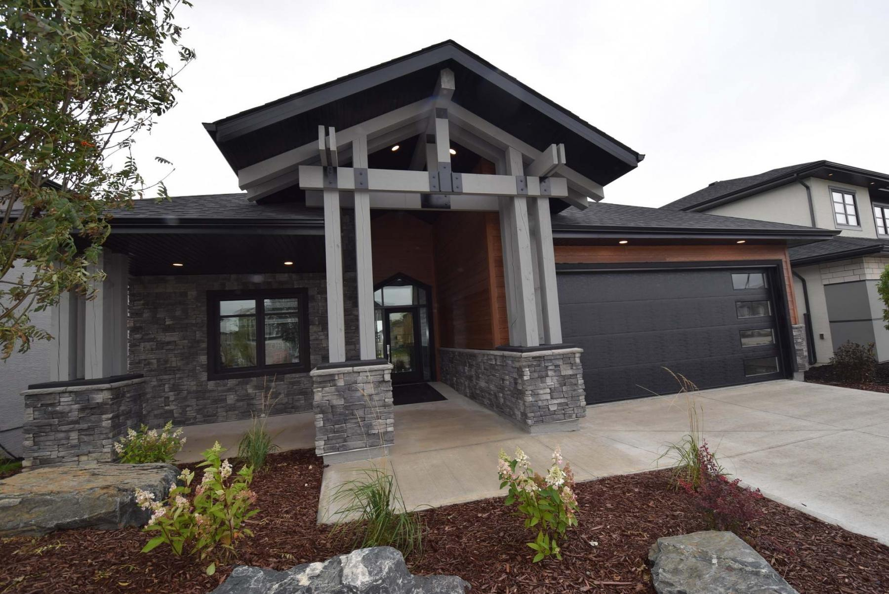 <p>TODD LEWYS / WINNIPEG FREE PRESS</p><p>The clean, linear design of 661 Bridge Lake Dr. starts with a classy, understated exterior. The entrance features a peaked roof with wooden pillars and beams and cultured stone trim.</p>