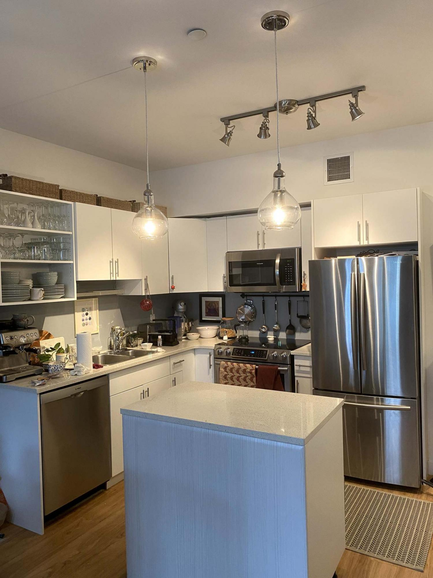 <p>Photos by Marc LaBossiere / Winnipeg Free Press</p><p>A decorative track light replaced an old kitchen fixture, while two fish-bowl pendants were introduced above the island.</p>