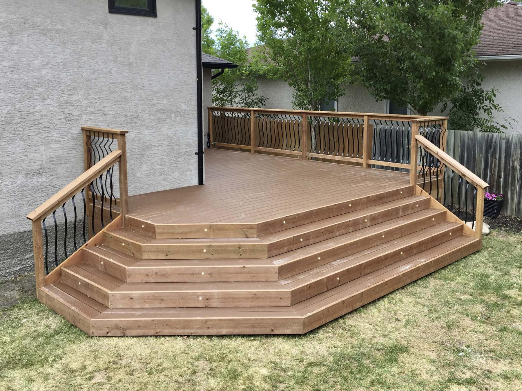 <p>Photos by Marc LaBossiere / Winnipeg Free Press</p><p>A 24-foot-by-16-foot L-shaped deck topped with TREX composite and brown-treated lumber fascia, partial wraparound stairs with flush-mount LED lighting and traditional wooden railings showcasing black metal profile balusters. </p></p>