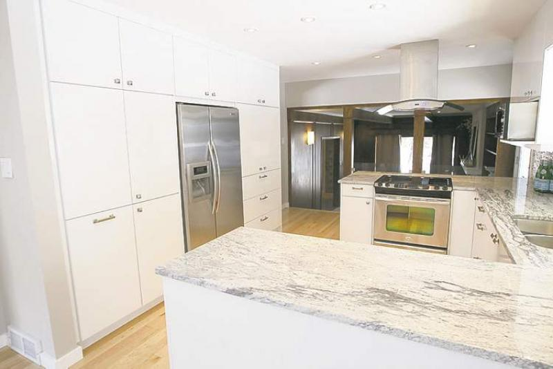 Grey Granite Countertops And White Thermofoil Cabinets Were Constructed To  Update The Peninsula Style Kitchen.