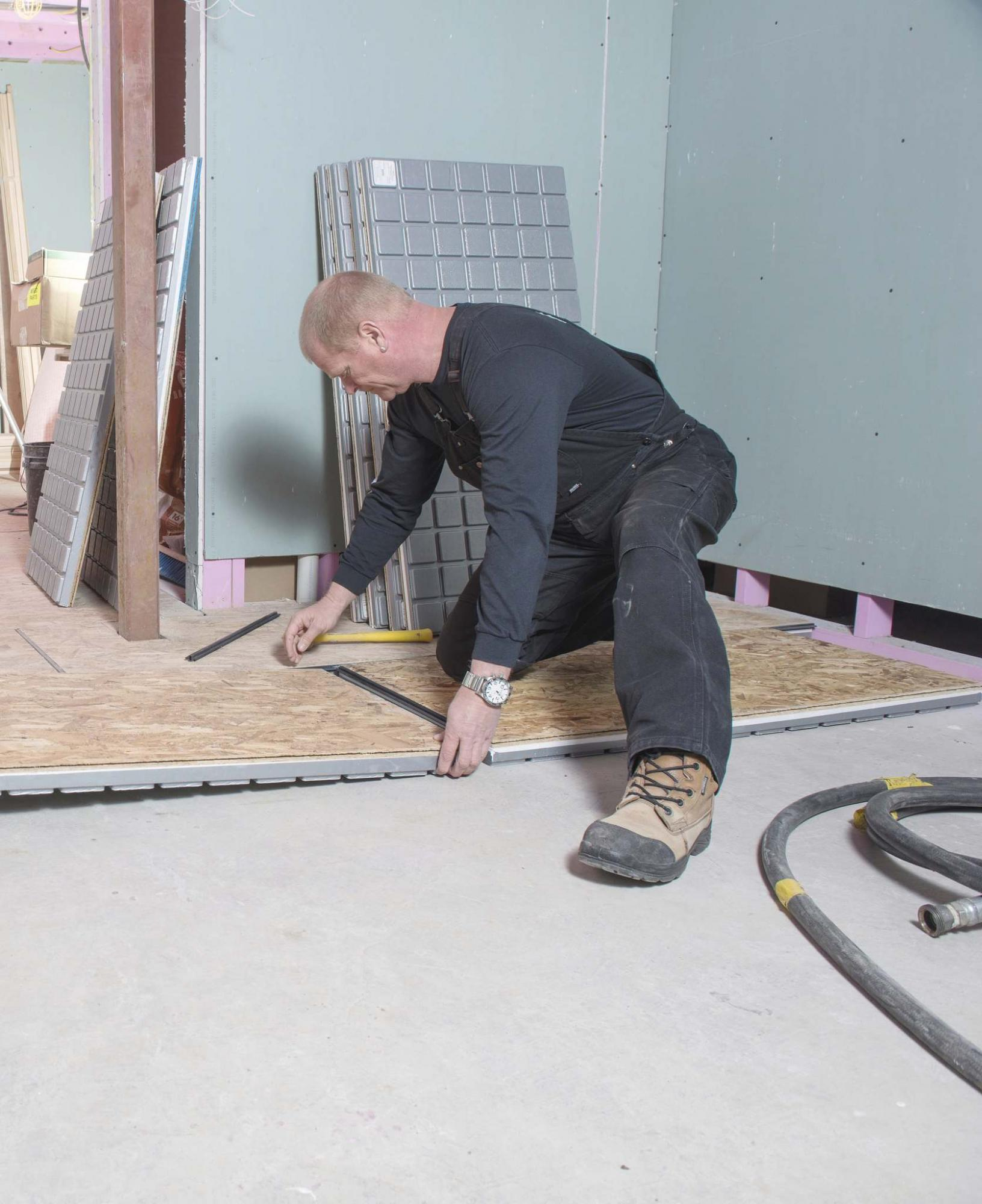 <p>Alex Schuldtz / Holmes Group</p><p>TV host and contractor Mike Holmes installs insulated subfloor panels in a basement. </p></p>