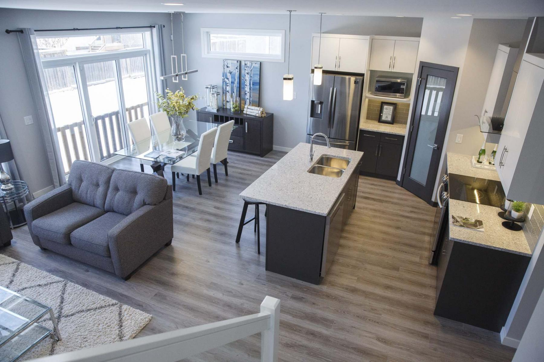 <p>The kitchen features off-white and dark taupe cabinets, which both pair nicely with the taupe quartz countertops and tile backsplash. (Mike Deal / Winnipeg Free Press)</p>