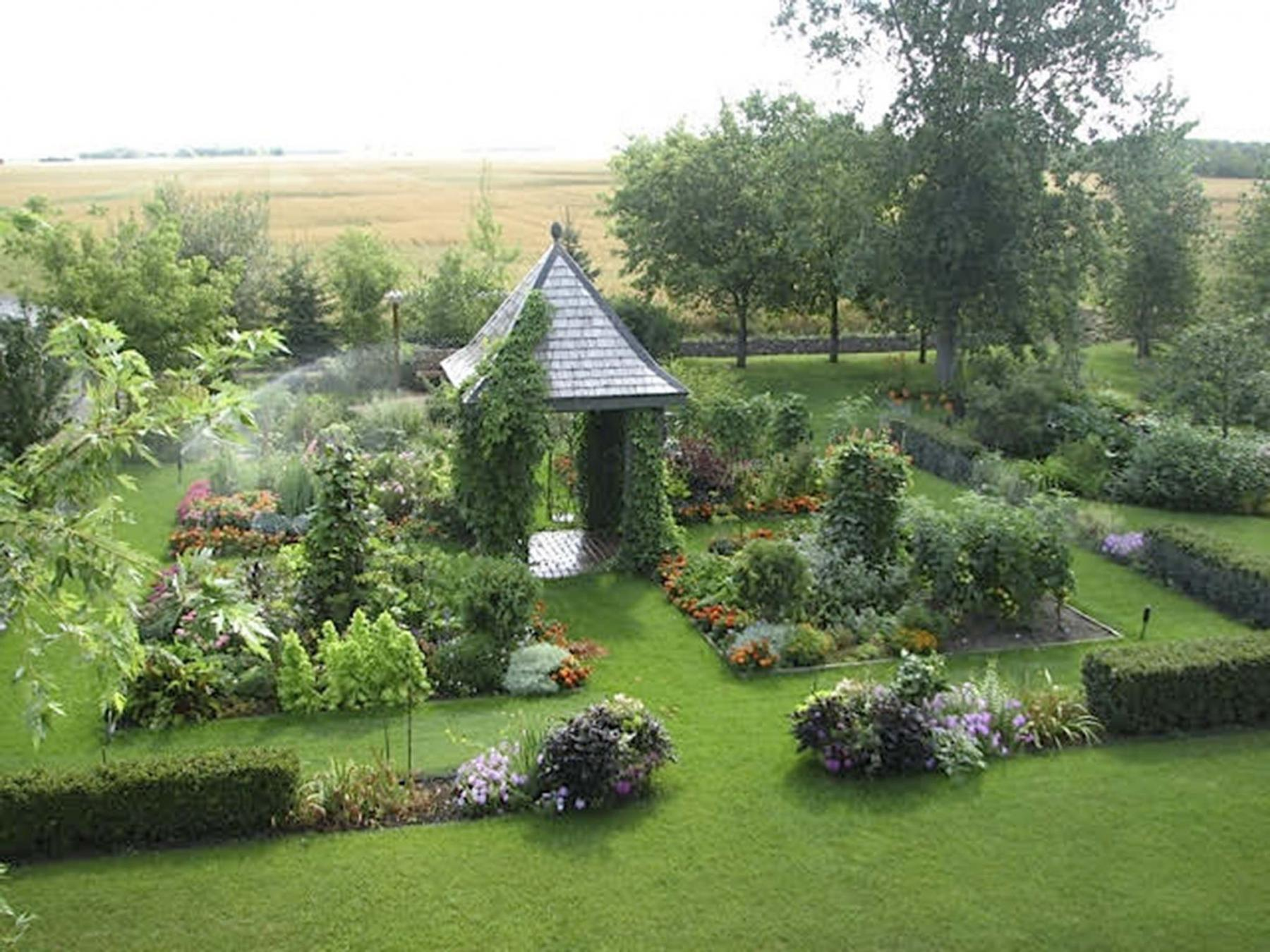 <p>A garden house sits in the centre of a parterre-like garden planted with perennials and vegetables.</p>