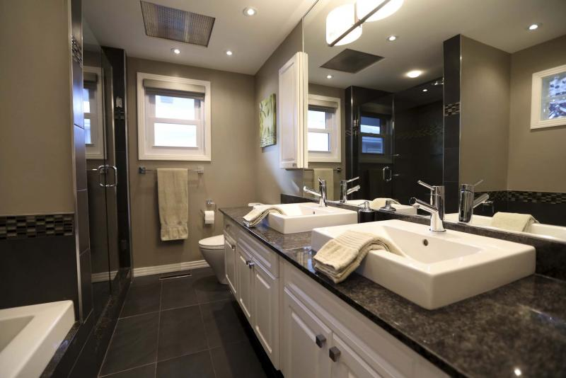<p>RUTH BONNEVILLE / WINNIPEG FREE PRESS</p><p>The bathroom includes a soaker tub set in mocha tile, a custom glass/tile shower and a white vanity with dual sinks on a granite countertop.</p></p>