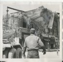Winnipeg Free Press Archives Time Building Fire  (10)  June 11, 1954 Part of the front wall of the Edwards block, gutted by fire, is sent crashing- to the ground' as three crane trucks with thousands of feet of steel cable tugged at its girders. Hundreds of onlookers pushed their way past police lines on Portage avenue to get a closer look at the wrecking crew's work. As the building fell, road, and pavement shuddered under the impact. fparchive