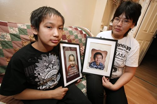 January 14, 2011 - 110113  -  On Friday, January 14, 2011 McLaine Flett and her son Ralph (10) pose for a picture in their home with photos of her son Nathanial who drowned in the Red River in early December of 2010. John Woods / Winnipeg Free Press