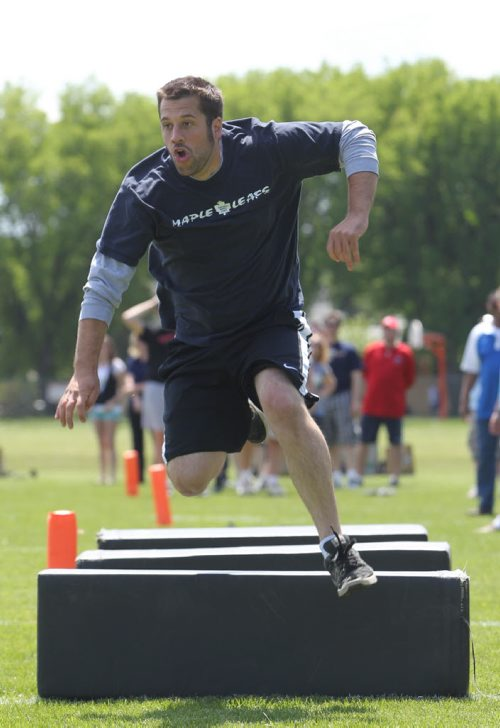 Brandon Sun 10062011 CKLQ sports reporter Tyler Crayston leaps over obstacle during the first annual Rod Hill/Blue Bomber Media challenge at Vincent Massey High School on Friday afternoon. The event was held in advance of the Blue Boombers Football Day in Brandon today in which the Bombers will hold training camp at Neelin high School and sign autograph's. High school football players from Neelin, Vincent Massey and Crocus Plains all competed in the event alongside members of the media. (Tim Smith/Brandon Sun)