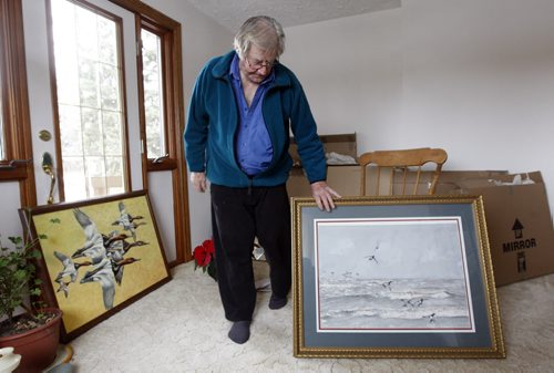 Delta Beach - Artist Peter Ward was forced from his home and studio in Delta  Marsh to  rent a home in Portage la Prairie by Lake Manitoba flodding , in pic he unpacks examples of his work . Delta Marsh artist  91 year old  Peter Ward  has been  put out of his  house  by Assiniboine River / Lake Manitoba flooding  continues to  go out to his  home  at the marsh and paint for a few hours each day .He lives in a rented house i Portage la Prairie  - Bill Redekop Story -  - KEN GIGLIOTTI /  WINNIPEG FREE PRESS /  Nov. 30  2011