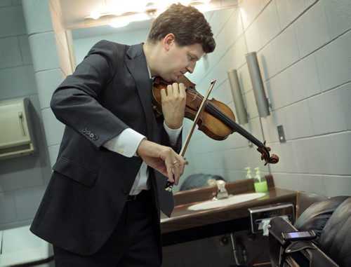 Brandon Sun Violinist James Ehnes practices on his Stradivarius violin as he catches up on a Detroit Tigers baseball game on his smartphone before a concert in October. (Colin Corneau/Brandon Sun)