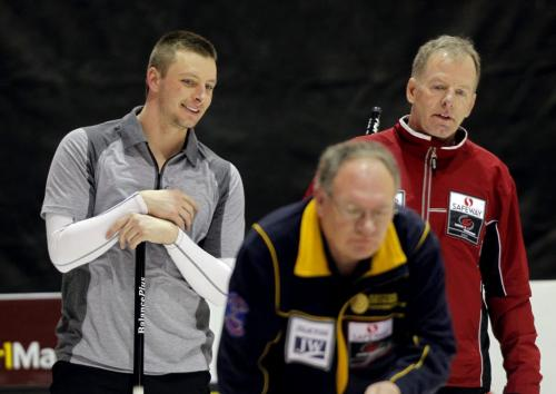 2012 Safeway Championship. Manitoba Men's Curling Championship in Dauphin, Manitoba. Vic Peters, in red, and his son Daley, in grey, in their first match Wednesday afternoon. The fella in Gerry Haight. February 8, 2012 BORIS MINKEVICH / WINNIPEG FREE PRESS