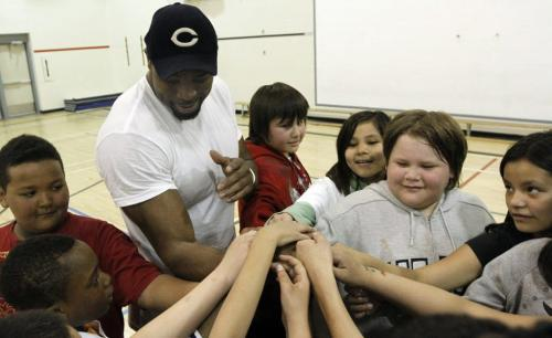 "Chicago Bears defensive end Israel Idonije leads a cheer with students at Sister MacNamara School on Friday. Idonije was named the school's ""principal for a day"" and participated in gym classes with the students throughout the morning. This event was in conjunction with the Israel Idonije Foundation First Down Attendance program, which encourages students to maintain regular school attendance and overall high achievement. May 04, 2012. SARAH O. SWENSON / WINNIPEG FREE PRESS"