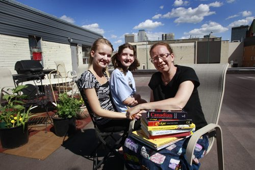 Francine Wiebe with her daughters  Katie,12 (centre ) and at left Alexandra,14, on the roof of their home. Francine Wiebe moved her husband and two daughters into an old building on Notre Dame so she could home school African immigrant kids. Lindor Reynolds story  (WAYNE GLOWACKI/WINNIPEG FREE PRESS) Winnipeg Free Press  June 28 2012