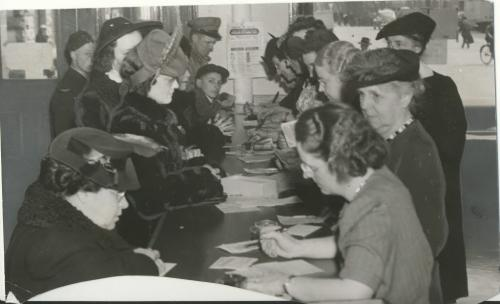 Winnipeg Free Press Archives Winnipeg WWII Home Front April 7, 1943 Anxious to put down fruit :for the coming winter, thousands of Winnipeg citizens, some of whom are seen above, are daily making application for extra sugar at the local ration board. 158 Princess street. While those seen above appeared 'in person, the number of applications being received through the mail is tremendous, William H. Florence, secretary of the board, states. Mr. Florence is seen in the lower picture, with a portion of Ihe mail lhal came in Tuesday. This mail is sorted and arranged in numerical order by volunteer workers under Mrs. John Allen, MJss Isabel Robson being in charge of the workers providing information at the telephone and counter. A great many applications are filled incorrectly, and have to be returned, Mr. Florence says. Also, residents of other sections of the province arc mailing their applications to the Winnipeg office, which should not be done.