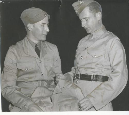 Winnipeg Free Press Archives Winnipeg WWII Home Front May 20, 1942 Designed for greater comfort, a new style khaki drill tunic soon will be issued to troops in Canada's  active army. The new tunic has  an open neck  instead of the closed  collar formerly worn. It has an attached cloth belt to replace the old leather make belt issued in 1915. Two extra side pockets are provided and the tunic will be worn with an issue shirt and black tie. Old style tunics will be  turned over to the reserve army. Sgt. Hugh Clarke, assistant forman of the Ordnance Clothing Corps clothing depot, wears the new tunic (left), while Pte. Burns, storeman at the depot wears the old style, (right).