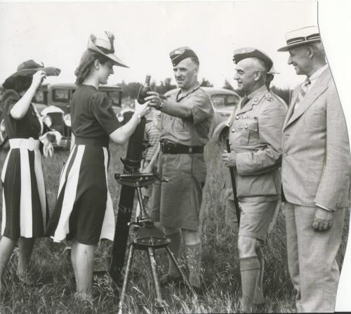 Winnipeg Free Press Archives Winnipeg WWII Home Front June 30, 1941 Beauty Pays Tribute to Soldiers of the King Mrs Ingram trys her hand at loading a trench mortar under the direction of Major R.H. Baxter commanding   Co. Infantry Training centre. R.G. Graham, officer Commanding Infantry Training Centre looks on.
