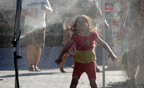 Fringe Festival Old Market Square stage - Megan Rodd, 5, cools off in a water sprayer.  July 19, 2012  BORIS MINKEVICH / WINNIPEG FREE PRESS
