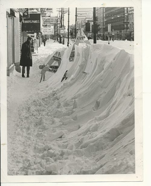 Jerry Cairns/Winnipeg Free Press Archives Winnipeg Blizzard (11) March 5, 1966 Surveying the results of Friday's blizzard was part of the game Saturday a pedestrians along Portage Avenue gaped in wonderment at snow hurled high long the sidewalks. fparchive
