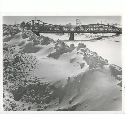 Winnipeg Free Press Archives Winnipeg Blizzard (18) March 10, 1966 Although mild weather has returned to Winnipeg, memories of  last week's storm still linger on city streets and along river banks. This picturesque but unwanted wintry scene shows snow piled high along the Red River. The picture was taken near the Louis Bridge, Higgins Avenue and Stadacona Street. fparchive